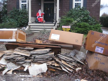 Stock Image of Flood debris awaits pickup as a Santa Claus is seen on the porch of a home in West Pittston, Pa. More than three months after Tropical Storm Lee flooded towns up and down the Susquehanna River, many residents are frustrated by the slow pace of recovery and will be out of their homes for Christmas
