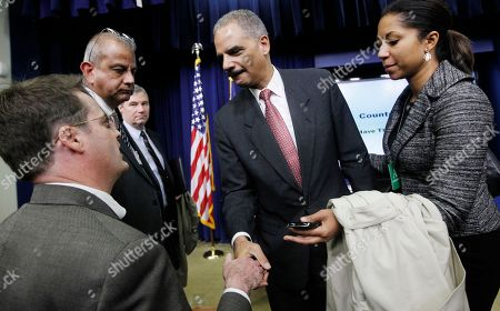 Eric Holder, Neil Munro Attorney General Eric Holder shakes hands with Daily Caller reporter Neil Munro, left, as Munro asks him about calls for Holder's resignation over an investigation of arms traffickers called Operation Fast and Furious after an event on counterfeit goods at the Eisenhower Executive Office Building across from the White House in Washington