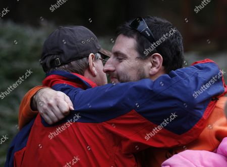 Stewart Schmidt hugs close friend David Entler after being found by rescuers, in Mount Hood National Forest, near Estacada, Ore. The Clackamas County sheriff's office says the father, son and daughter were seen from the air on Tuesday afternoon. Search crews then met them, confirmed they were in good condition and took them to reunite with other family members. The three are 33-year-old Stewart Schmidt, his 15-year-old son, Gabriel McCoy, and 6-year-old daughter, Aidan Schmidt. They were found near Timothy Lake in Mount Hood National Forest. They were reported missing Monday night