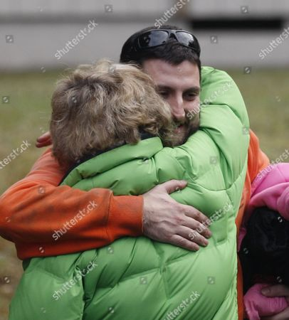Stewart Schmidt hugs close friend Terri Entler after being found by rescuers, in Mount Hood National Forest, near Estacada Ore. The Clackamas County sheriff's office says the father, son and daughter were seen from the air on Tuesday afternoon. Search crews then met them, confirmed they were in good condition and took them to reunite with other family members. The three are 33-year-old Stewart Schmidt, his 15-year-old son, Gabriel McCoy, and 6-year-old daughter, Aidan Schmidt. They were found near Timothy Lake in Mount Hood National Forest. They were reported missing Monday night