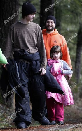 Stewart Schmidt walks with his 15-year-old son, Gabriel McCoy, and 6-year-old daughter, Aidan Schmidt after being found by rescuers, in Mount Hood National Forest, near Estacada Ore. The Clackamas County sheriff's office says the father, son and daughter were seen from the air on Tuesday afternoon. Search crews then met them, confirmed they were in good condition and took them to reunite with other family members. The three were found near Timothy Lake in Mount Hood National Forest. They were reported missing Monday night