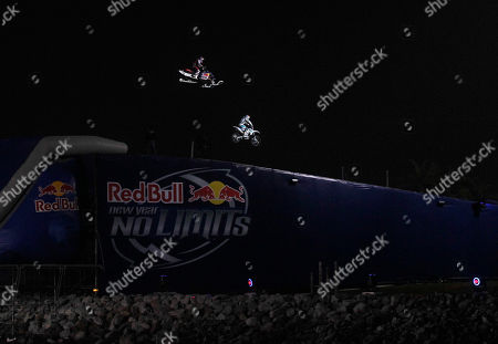 "Stock Photo of Robbie Maddison, Levi LaVallee Motorcyclist Robbie Maddison and snowmobiler Levi LaVallee preparet to land after jumping over a water gap as part of the ""Red Bull: New Year. No Limits"" series, in San Diego. LaVallee jumped 412 feet and Maddison jumped 378 feet on the jump"