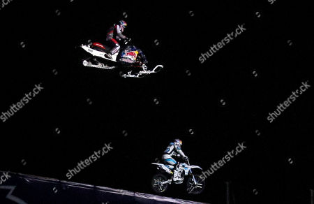 "Stock Picture of Robbie Maddison, Levi LaVallee Motorcyclist Robbie Maddison, below, and snowmobiler Levi LaVallee prepare to land after jumping over a water gap as part of the ""Red Bull: New Year. No Limits"" series, in San Diego"