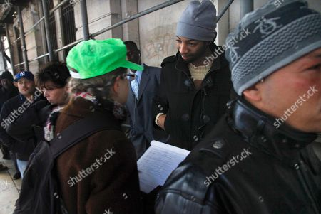 Hero Vincent, second from right, an early protester in the Occupy Wall Street movement, listens as Judith Anderson, left, a lawyer working with the National Lawyers Guild, records information about him as he stands on line outside Manhattan Criminal Court on in New York. Protesters are answering summons stemming from their mass arrest during a march across the Brooklyn Bridge last October