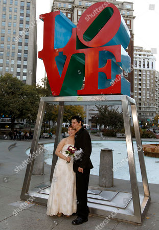 """Alicia """"Ally"""" Nauss, Adam Hill Alicia """"Ally"""" Nauss, left, and Adam Hill pose for photos in front of the famous Love sculpture after they were married at the Occupy Philadelphia encampment in front of City Hall in Philadelphia. Nauss and Hill met while working the information tent at Occupy Philadelphia. The encampment at City Hall is one of many being held across the country similar to the ongoing Occupy Wall Street demonstration in New York"""