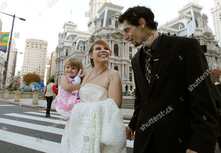 """Alicia """"Ally"""" Nauss, Adam Hill Alicia """"Ally"""" Nauss, left, carrying her daughter Rhys Corcoran, age 2 and a half, and Adam Hill walks across the street after they were married at the Occupy Philadelphia encampment in front of City Hall in Philadelphia. Nauss and Hill met while working the information tent at Occupy Philadelphia. The encampment at City Hall is one of many being held across the country similar to the ongoing Occupy Wall Street demonstration in New York"""