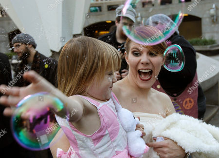 """Alicia """"Ally"""" Nauss, Rhys Corcoran Alicia """"Ally"""" Nauss and her daughter Rhys Corcoran, age 2 and half, play with bubbles after Nauss and Adam Hill were married at the Occupy Philadelphia encampment in front of City Hall in Philadelphia. Nauss and Hill met while working the information tent at Occupy Philadelphia. The encampment at City Hall is one of many being held across the country similar to the ongoing Occupy Wall Street demonstration in New York"""