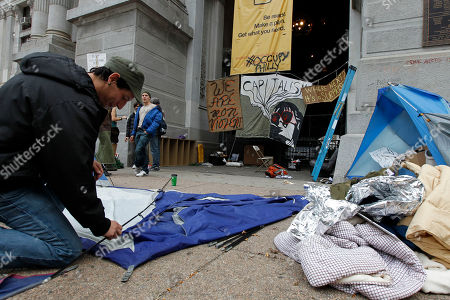 Adam Hil Adam Hill takes down his tent at the Occupy Philadelphia encampment at City Hall in Philadelphia. Dozens of Occupy Philadelphia protesters planned to try to hold down their encampment outside City Hall on Monday, a day after a city-imposed deadline passed for them to leave