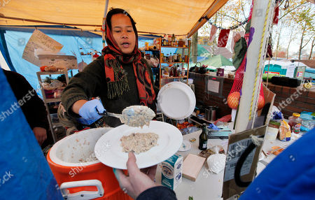 Maria Arceo Gardner serves oatmeal to a camper at Occupy Seattle at Seattle Central Community College Tuesday morning, in Seattle. Officials at the college said last week that they're getting fed up with Occupy Seattle. The protesters moved their encampment to the school late last month after city officials told them they couldn't pitch overnight tents in a downtown park. The college estimates the demonstration is costing it $20,000 a week