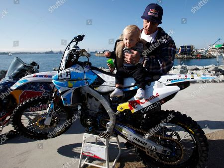 "Robbie Maddison Motorcyclist Robbie Maddison puts his son Kruze, 1, on his bike during a news conference for his upcoming jump with snowmobiler Levi LaVallee, in San Diego. The riders plan to jump across a harbor entrance on the San Diego Bay before midnight on New Year's Eve as part of the ""Red Bull: New Year. No Limits"" event"