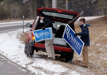 Stock Picture of John Phelan, Tyler Becker John Phelan, a Romney campaign volunteer from Alexandra, Va., left, and Tyler Becker, a volunteer from Weare, N.H., carry yard signs they are placing along I-93 in Tilton, N.H., . Romney is hosting a Spaghetti dinner at the Tilton School Friday night