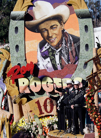 """Roy Rogers Jr., right, and his son Dustin Rogers wave as they sing """"Happy Trails"""" aboard the RFD-TV float, in honor of the centenary of the cowboy star's birth, in the 123rd Rose Parade in Pasadena, Calif., . The float won the Tournament Special trophy"""