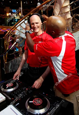 """Stock Image of Rick Scott, Ro Parrish Florida Gov. Rick Scott, center, learns how to work the turntable with D.J. Ro Parrish during his """"workday"""" as a D.J. aboard the Carnival Cruise Lines' ship """"Carnival Imagination,"""" at the Port of Miami in Miami. Since August, Scott, a Republican, has been making similar stops across the state to work jobs with regular Floridians. He borrowed the idea from former Gov. and U.S. Sen. Bob Graham, a Democrat, and renamed the plan to coincide with his campaign slogan: """"Let's Get to Work"""