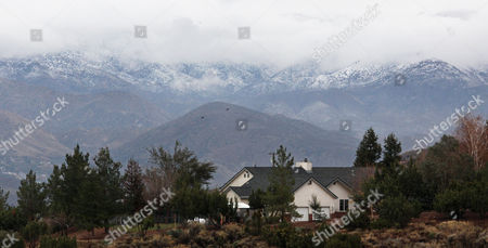 The north-facing slopes of the San Gabriel Mountains have a dusting of snow as clouds obscure the peaks, seen from Acton, Calif., as a late autumn storm passes through Southern California . The National Weather Service says the storm that moved in before dawn Monday will provide a quarter-inch to three-quarters of an inch of rain in many Los Angeles County locations and an inch or more in the mountains