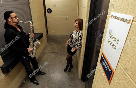 Stock Picture of Saxophonist Alto Reed practices the National Anthem while his fiance, Christiana Van Ryn, listens during a rain delay before the start of Game 4 of baseball's American League championship series between the Detroit Tigers and Texas Rangers, in Detroit