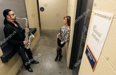 Stock Picture of Saxophonist Alto Reed practices the national anthem while his fiance, Christiana Van Ryn, listens during a rain delay before Game 4 of baseball's American League championship series between the Detroit Tigers and Texas Rangers, in Detroit