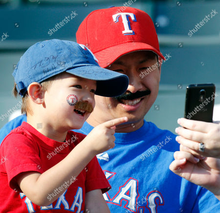 Michael Wang and his son, Alex, 2, look at themselves in a photo before Game 2 of baseball's American League division series playoffs against the Tampa Bay Rays and the Texas Rangers, in Arlington, Texas. They were emulating Rangers pitcher Derek Holland who has been trying to grow a mustache