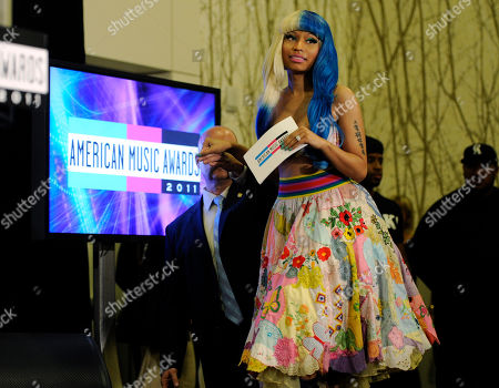 Nicky Minaj Nicky Minaj is helped onto the stage to announce nominations for the 2011 American Music Awards, in Los Angeles. The awards will be held in Los Angeles on November 20