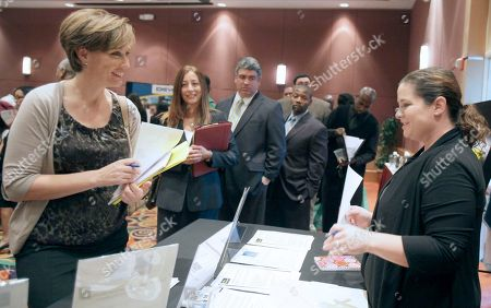 Stock Picture of Lisa Flemion, left, talks with Jessica Stone, a recruiter for High Voltage Staffing, a company that matches job applicants with employers, at a job fair at the Crowne Plaza Hotel in Orlando, Fla. Employers added 103,000 jobs in September, a modest burst of hiring after a sluggish summer