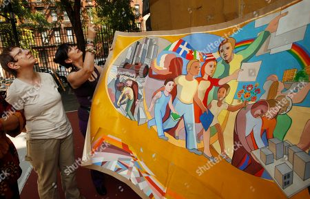 "Stock Picture of Art conservator Harriet Irgang Alden, left, and Patricia Quijano Ferrer, widow of Arnold Belkin, compare a painting done in preparation for Belkin's now-decaying 1972 mural ""Against Domestic Colonialism,"" against the full-sized work, at the May Matthews /Alexandra Palmer park playground in New York. Alden, an architect, and an artist familiar with Belkin's work are exploring whether the mural, which the Washington, D.C.-based Heritage Preservation has called one of the country's most endangered public murals, can be restored"