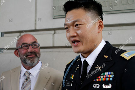 """Dan Choi, Robert Feldman Former Army Lt. Dan Choi, right, an openly gay Iraq war veteran who protested the military's """"don't ask, don't tell"""" policy by handcuffing himself to a White House fence, speaks to the media with his lawyer, Robert Feldman, after the start of his trial in Washington, on . Choi is charged with failing to obey a police officer's order to leave the grounds. He and 12 others chained themselves to the White House fence in November 2010 during a protest"""