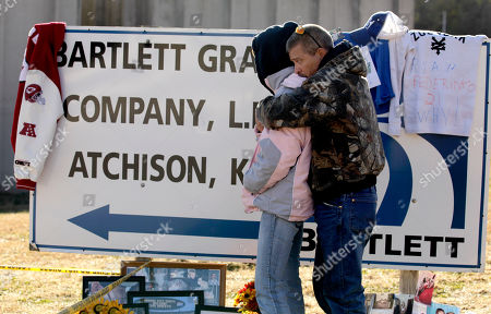 Zoe Bock is comforted by her husband Kevin Bock at a makeshift memorial outside the Bartlett Grain Company in Atchison, Kan. . Three people, including Zoe Bock's son Chad Roberts, 20, are confirmed dead and three others missing in the aftermath of an explosion at the facility Saturday night. Emergency personnel are now in a recovery operation for the three missing individuals