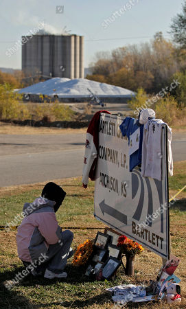 Zoe Bock looks at a makeshift memorial outside the Bartlett Grain Company in Atchison, Kan. . Three people, including Bock's son Chad Roberts, 20, are confirmed dead and three others missing in the aftermath of an explosion at the facility Saturday night. Emergency personnel are now in a recovery operation for the three missing individuals