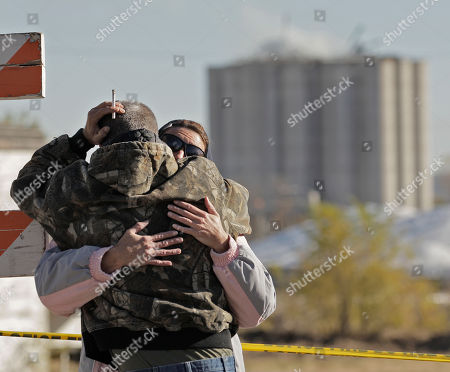 Zoe Bock is comforted by her husband Kevin Bock outside the Bartlett Grain Company in Atchison, Kan. . Three people, including Zoe Bock's son Chad Roberts, 20, are confirmed dead and three others missing in the aftermath of an explosion at the facility Saturday night. Emergency personnel are now in a recovery operation for the three missing individuals