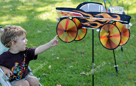 Mario Galla checks out a hot rod style garden spinner while shopping with his mother, Linda Leone, not shown, on a warm sunny day in Clarence, N.Y
