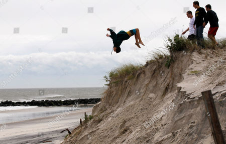 Connor Robinson Connor Robinson does a back flip landing in the soft recently eroded sand as his friends Connor McGlynn, left, Topher Bates, and Ray Smith, right, stand nearby after Hurricane Irene, on Long Beach Island in Long Beach Township, N.J