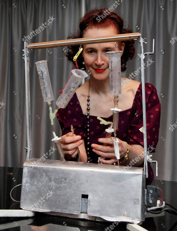 """Ava Janus, Thanatron Ava Janus of Troy, Mich., the sole surviving heir of Dr. Jack Kevorkian, poses with his """"Thanatron"""" machine, in New York . It is scheduled to be auctioned as part of his estate, Friday Oct. 28, 2011. Kevorkian's estate is going ahead with plans to auction 17 of his paintings, including one he did with a pint of his blood, even though a suburban Boston museum is refusing to give them up"""