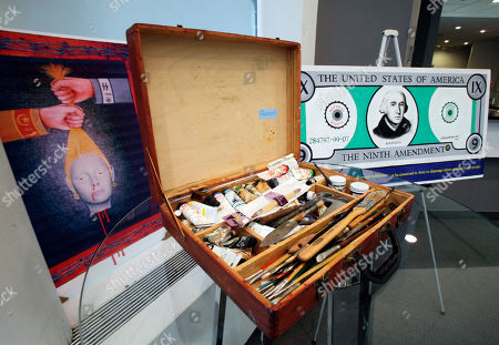 """A wooded paint carrying case, is flanked by the paintings """"Genocide,"""" left, and """"9th Amendment,"""" from Dr. Jack Kevorkian's estate, scheduled to be auctioned, are displayed in New York, Thursday, Oct. 27, 2011. Kevorkian's estate is going ahead with plans to auction 17 of his paintings, including one he did with a pint of his blood, even though a suburban Boston museum is refusing to give them up"""