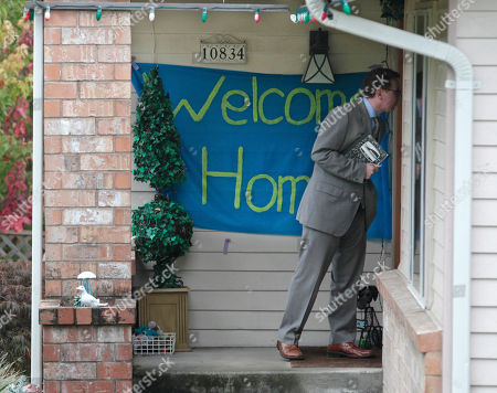 """A reporter knocks on the door where a """"welcome home"""" sign is posted at the home of Curt Knox for his daughter Amanda Knox on her expected arrival later in the day, in Seattle. It's been four years since the University of Washington student left for the study abroad program in Perugia and landed in prison. The group Friends of Amanda Knox and others have been awaiting her return since an Italian appeals court on Monday overturned her conviction of sexually assaulting and killing her British roommate"""