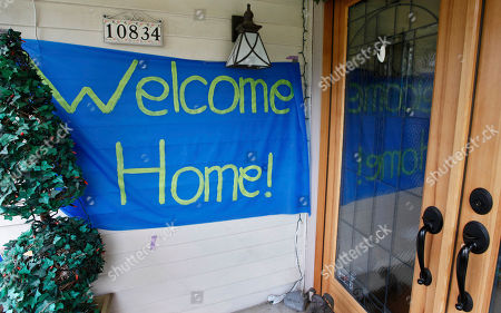 """A """"welcome home"""" sign is posted at the home of Curt Knox for his daughter Amanda Knox on her expected arrival later in the day, in Seattle. It's been four years since the University of Washington student left for the study abroad program in Perugia and landed in prison. The group Friends of Amanda Knox and others have been awaiting her return since an Italian appeals court on Monday overturned her conviction of sexually assaulting and killing her British roommate"""
