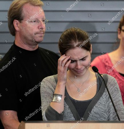 Curt Knox As her father, Curt Knox, stands behind, Amanda Knox tries to gain her composure to make a statement during a news conference shortly after her arrival at Seattle-Tacoma International Airport, in Seattle. Knox was freed Monday after an Italian appeals court threw out her murder conviction for the death of her British roommate, Meredith Kercher