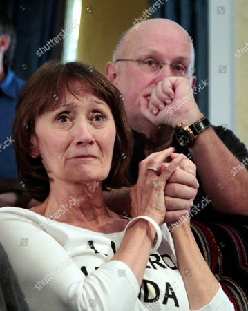 Susan Rosales, left, and Tom Wright holds hands as they watch a television news broadcast about the Amanda Knox appeal verdict from a hotel suite in downtown Seattle . An Italian appeals court has thrown out Knox's murder conviction and ordered the young American free after nearly four years in prison for the death of her British roommate, Meredith Kercher