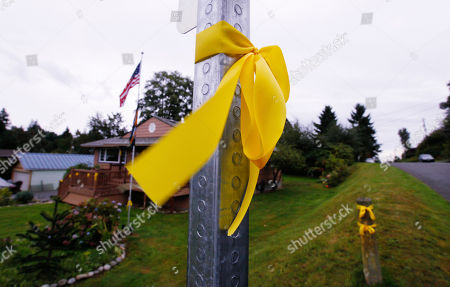 A yellow ribbon flutters on a post down the street from the home of Curt Knox, the father Amanda Knox, Wednesday morning, in Seattle. Knox's life turned around dramatically Monday when an Italian appeals court threw out her conviction in the sexual assault and fatal stabbing of her British roommate, Meredith Kercher. On Tuesday, the day that she returned home to Seattle, photos of her crying in the courtroom after the verdict was read appeared on the front pages of newspapers in Italy, the U.S., Britain and around the world