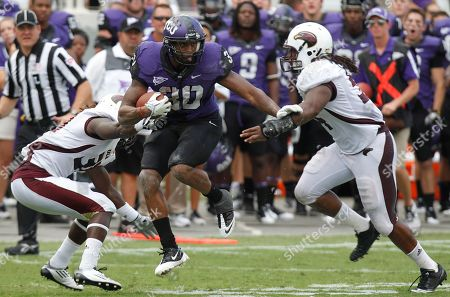 Stock Photo of Aundre Dean, Darius Prelow TCU running back Aundre Dean (30) runs between Louisiana Monroe safety Darius Prelow, left, and linebacker Jason Edwards (54) during the second half of their NCAA college football game in Fort Worth, Texas, . TCU won 38-17