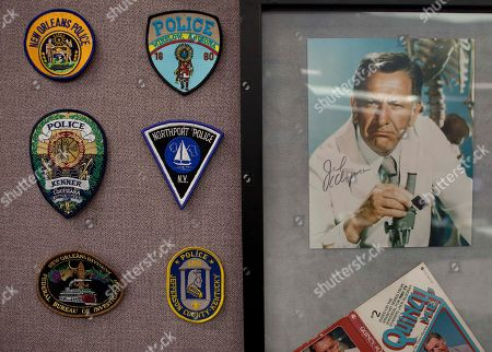 Patches from different police departments and a portrait of Jack Klugman who played the television character of Quincy, a medical examiner, adorn the cubicle of an employee at the Clark County Coroner's office, in Las Vegas. The coroner's office investigates about 3,500 of the14,000 people who die each year in and around Las Vegas.The official whose name goes on thousands of death certificates each year recently inked a deal with a the Discovery Channel for a series of TV episodes featuring the work of the Sin City coroner's office