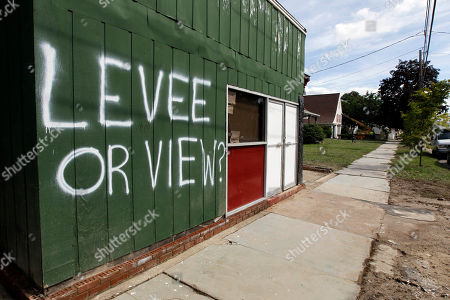 """A sign on a wall asks the question """"Levee or View?"""" in West Pittston, Pa., after homes were damaged by floodwaters from the Susquehanna River, swollen after the remnants of Tropical Storm Lee came through. While many people in West Pittston did oppose a $25 million levee system when it was discussed a generation ago - among them occupants of the stately riverfront Victorians that line the borough's nicest street, Susquehanna Avenue - it was the U.S. Army Corps of Engineers that made the ultimate decision to leave the borough unprotected"""