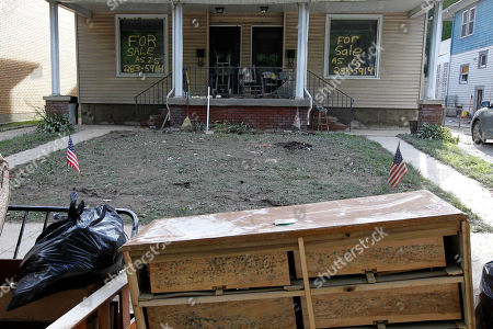 """A home sits for sale """"as is"""" with mold growing on the furniture out front, in West Pittston, Pa. Homes were damaged by floodwaters from the Susquehanna River swollen after the remnants of Tropical Storm Lee came through"""