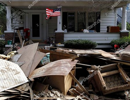 An American flag flies on a home with ruined items on the curb for collection in West Pittston, Pa. Homes were damaged by floodwaters from the Susquehanna River swollen after the remnants of Tropical Storm Lee came through