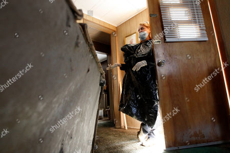 Connie Andrews Connie Andrews wears gloves, a mask and a trash bag as she pauses while cleaning out her home in West Pittston, Pa. Homes were damaged by floodwaters from the Susquehanna River swollen after the remnants of Tropical Storm Lee came through