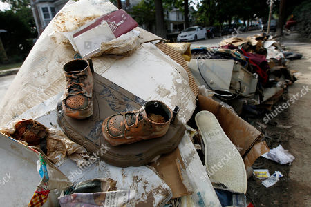 Bronzed baby shoes coated with mud are put on the curb for collection in West Pittston, Pa., where homes were damaged by floodwaters from the Susquehanna River, swollen after the remnants of Tropical Storm Lee came through. While many people in West Pittston did oppose a $25 million levee system when it was discussed a generation ago - among them occupants of the stately riverfront Victorians that line the borough's nicest street, Susquehanna Avenue - it was the U.S. Army Corps of Engineers that made the ultimate decision to leave the borough unprotected