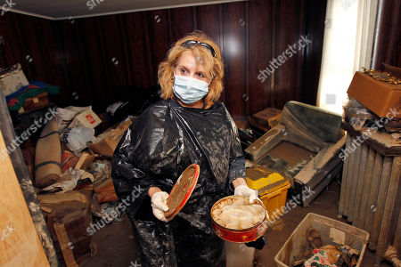 Connie Andrews Connie Andrews wears gloves, a mask, and a trash bag as she looks at a cookie tin filled with water while cleaning out her home in West Pittston, Pa. Homes were damaged by floodwaters from the Susquehanna River swollen after the remnants of Tropical Storm Lee came through. While many people in West Pittston did oppose a $25 million levee system when it was discussed a generation ago - among them occupants of the stately riverfront Victorians that line the borough's nicest street, Susquehanna Avenue - it was the U.S. Army Corps of Engineers that made the ultimate decision to leave the borough unprotected