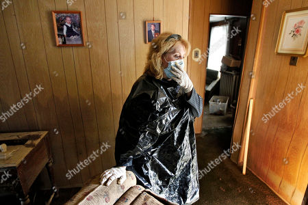Connie Andrews Connie Andrews wears a trash bag, gloves and a mask as she pauses while cleaning up her home in West Pittston, Pa. The area was damaged by flood waters from the Susquehanna River swollen after the remnants of Tropical Storm Lee came through