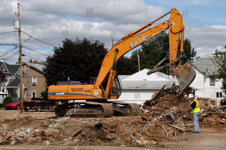 A steam shovel is used to demolish what was once a home and a business in West Pittston, Pa. The area was damaged by flood waters from the Susquehanna River swollen after the remnants of Tropical Storm Lee came through
