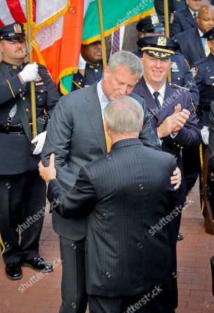 Incoming New York Police Department Commissioner James O'Neill, right, applauds as Mayor Bill de Blasio, center, speaks with outgoing police Commissioner William Bratton, during a ceremony marking Bratton's last day at police headquarters, in New York