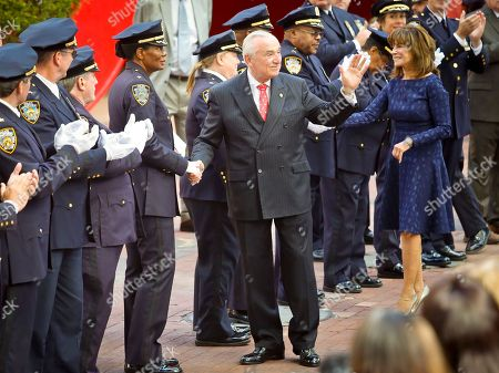 New York Police Department Commissioner William Bratton, center, accompanied by his wife Rikki Klieman, shake hands and acknowledged the applause of officers and commanders in dress blue uniforms during a ceremony, as he left police headquarters on his last day on the job, in New York
