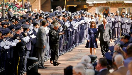 Hundreds of officers and commanders in dress blue uniforms applauded and saluted New York Police Department Commissioner William Bratton, as he walked with his wife Rikki Klieman in a ceremony on his last day on the job, at police headquarters in New York